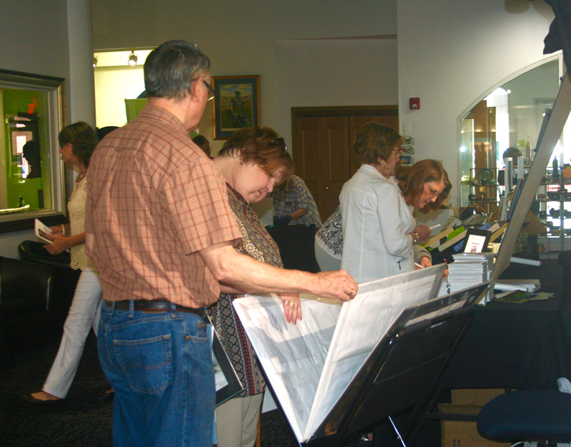 Guests at the Parkersburg Art Center browse through a bin of available work by exhibiting Aqueous 2018 artists.