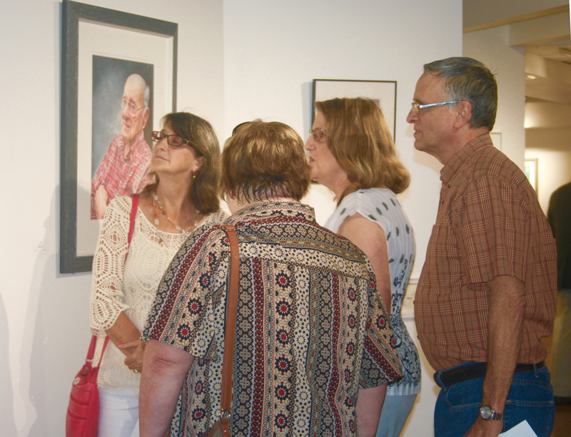 A group looks at the artwork in Aqueous 2018.