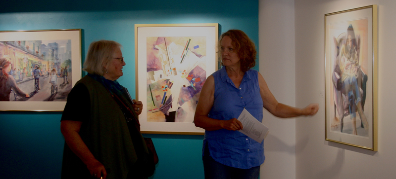 WVWS members Brenda Beatty and Deborah Lester discuss the paintings on display for Aqueous 2018.