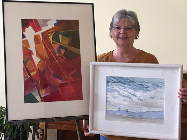 "Christine Rhodes with her watercolors ""The Best Laid Plans"" and ""Fishing Expedition."""